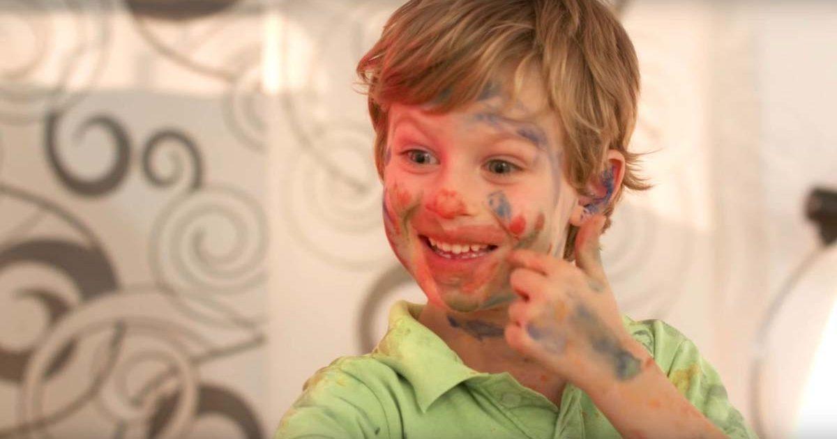 Junge hat sich das Gesicht bemalt mit Fingerfarben