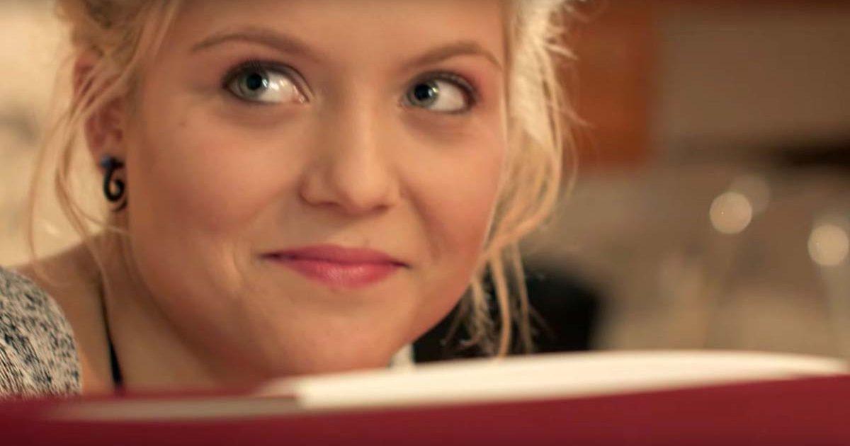 Junge Frau liest in einem Buch und schaut auf